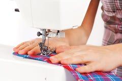 Mains d'une ouvrière couturière à la machine à coudre Photo stock