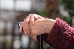 Mains d'une personne âgée sur la canne Photo libre de droits