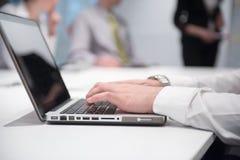Mains dactylographiant sur l'ordinateur portable lors de la réunion Photos libres de droits