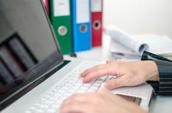 Mains dactylographiant sur un clavier d'ordinateur portable Photos libres de droits