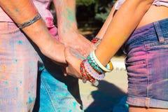 Mains dans des couples d'amour au festival de couleurs Holi Photographie stock libre de droits