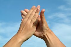 Mains dans des mains contre le ciel Image stock