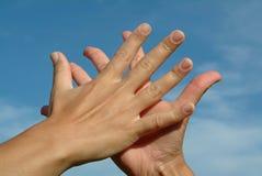 Mains dans des mains contre le ciel, concept d'amitié Photographie stock