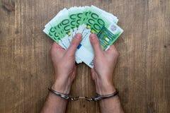 Mains dans des menottes avec l'argent images libres de droits