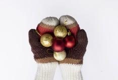 Mains dans des mitaines tricotées avec des boules de Noël sur le fond blanc Images libres de droits