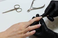 Mains dans des soins de gants au sujet des clous de mains Salon de beaut? de manucure Classement de clous avec le dossier photographie stock