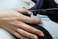 Mains dans des soins de gants au sujet des clous de mains Salon de beaut? de manucure Classement de clous avec le dossier photos stock