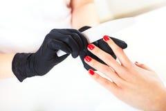 Mains dans des soins de gants au sujet des clous de mains Salon de beauté de manucure photographie stock libre de droits