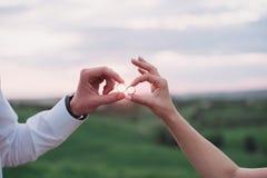 Mains dans l'amour - anneau de mariage avec la main humaine sur la lumière de coucher du soleil Images stock