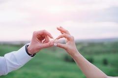Mains dans l'amour - anneau de mariage avec la main humaine sur la lumière de coucher du soleil Image stock