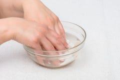 Mains dans l'eau avec des coquillages photos stock
