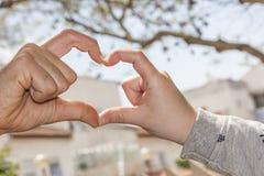 Mains dans la forme de coeur Images stock