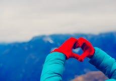 Mains dans la forme de coeur en nature d'hiver Voyage de montagnes d'amour Image stock