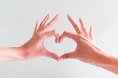 Mains dans la forme du coeur d'amour Images stock