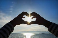 Mains dans la forme du coeur d'amour Photos stock