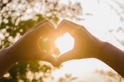 Mains dans la forme du coeur et du soleil d'amour Photos stock