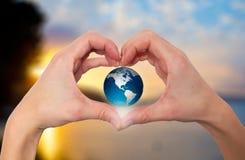 Mains dans la forme du coeur tenant le globe vert avec le backgrou de nature Image stock