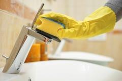 Mains dans les gants avec le tuyau et le robinet de nettoyage d'éponge image libre de droits