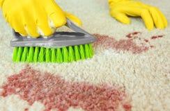 Mains dans les gants en caoutchouc nettoyant le tapis avec la brosse photo stock