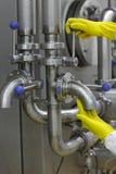 Mains dans les gants jaunes sur la prise et le levier du système technologique Images stock