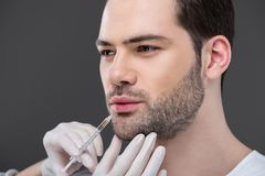mains dans les gants médicaux faisant l'injection de beauté pour l'homme barbu, photos libres de droits