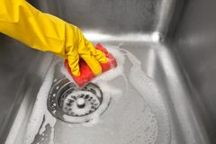 Mains dans les gants nettoyant l'évier de cuisine photos stock