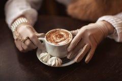 Mains dans les gants tenant une tasse de café Images libres de droits
