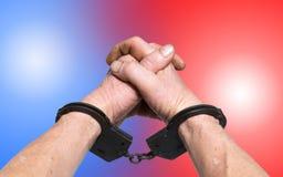 Mains dans les menottes et les lumières de police Photographie stock