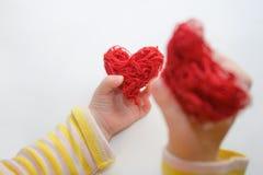 Mains de bébé tenant un coeur rouge Photo libre de droits