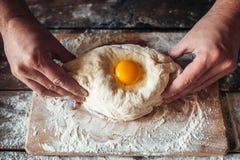 Mains de Baker préparant le khachapuri sur la table de cuisine Photos stock
