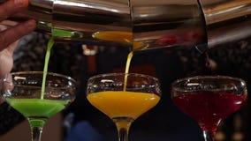Mains de barman versant trois cocktails colorés simultanément clips vidéos