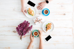 Mains de café de couples et des croissants potables de consommation sur la table images libres de droits