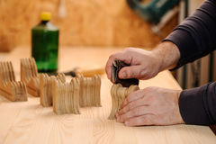 Mains de charpentier polissant le bois avec le papier sablé Photographie stock libre de droits
