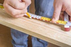 Mains de charpentiers avec le crayon et la bande de mesure image stock