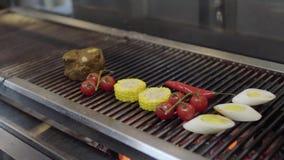 Mains de chef mettant le légume sur le gril dans le plan rapproché de cuisine de restaurant Faites cuire griller le maïs, tomates banque de vidéos