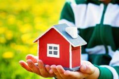 Mains de Childs tenant la maison modèle rouge Photo stock