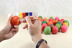 Mains de chrétien tenant des oeufs et les colorant avec le pinceau sur la table avec le fond de l'espace de copie photographie stock libre de droits