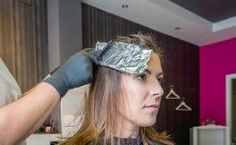 Mains de coiffeur enveloppant des cheveux de femme avec Photos stock