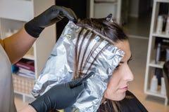 Mains de coiffeur séparant des cheveux de femme avec Photos stock