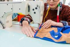 Mains de concepteur de femme tenant concevoir l'habillement Photographie stock