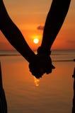 Mains de couples de silhouettes Photos stock