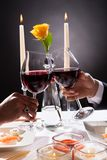 Mains de couples grillant le vin Photographie stock