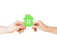 Mains de couples tenant la maison verte Photos stock
