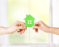 Mains de couples tenant la maison verte Image stock