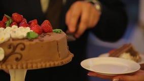 Mains de coupure de mariée et de marié d'une part d'un gâteau de mariage Coupez le gâteau de mariage les gens ont coupé et ont mi banque de vidéos