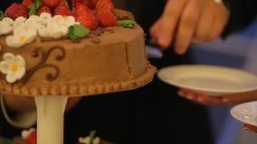 Mains de coupure de mariée et de marié d'une part d'un gâteau de mariage Coupez le gâteau de mariage les gens ont coupé et ont mi Photos stock