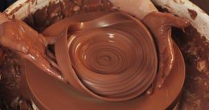 Mains de cruche d'argile de coupures de potier sur la roue de potier Formation de poterie, fin  banque de vidéos