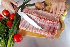 Mains de cuisinier avec de la viande crue Photographie stock libre de droits