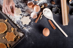 Mains de cuisinier, faisant des gaufres sur le tableau noir à partir du dessus Image stock