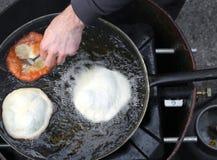 Mains de cuisinier faisant frire le grand frybread dans une casserole d'huile chaude image libre de droits